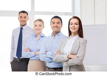 smiling businesswoman in office with team on back