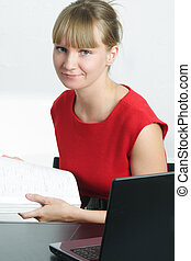 Smiling businesswoman in red holding magazine