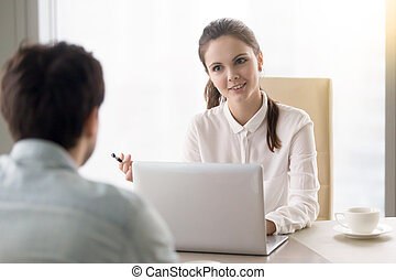 Smiling businesswoman interviewing a job applicant, business mee