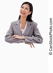 Smiling businesswoman leaning on a blank wall