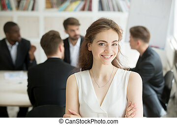 Smiling businesswoman looking at camera, team meeting at backgro