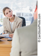Smiling businesswoman looking at interviewee