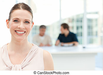 Smiling businesswoman looking at the camera while her ...