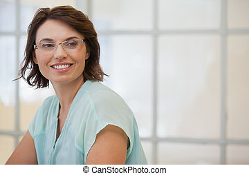 Smiling businesswoman looking away in office