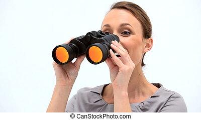 Smiling businesswoman looking through binoculars