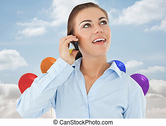 Smiling businesswoman looking upwards while on her phone against balloons in the sky