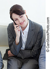 Smiling businesswoman on phone while waiting for a job interview in an office