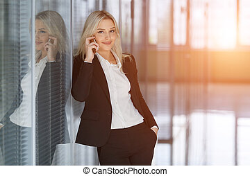 Smiling businesswoman on the phone looking at camera in an office
