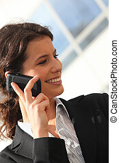 Smiling businesswoman on the phone outside an office building