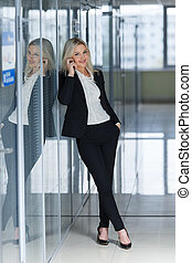 Smiling businesswoman on the phone standing at full height and looking at camera in an office