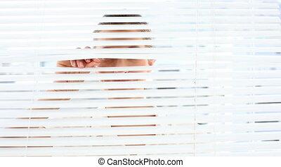 Smiling businesswoman peeking through blinds - Smiling...