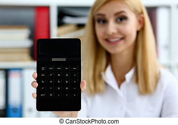 Smiling businesswoman portrait holds calculator in han
