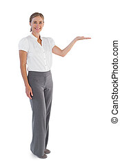 Smiling businesswoman presenting something with her hand