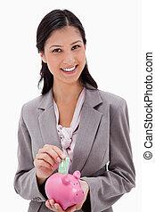 Smiling businesswoman putting money into piggy bank