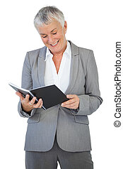 Smiling businesswoman reading notepad