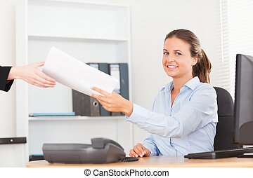 smiling businesswoman receiving a pile of paper looking into the camera in her office