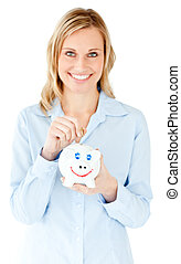 Smiling businesswoman saving money in a piggy-bank against ...