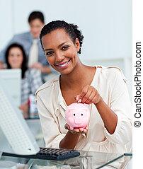 Smiling businesswoman saving money in a piggy-bank