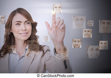 Smiling businesswoman selecting digital interface showing...