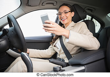 Smiling businesswoman sending a text message