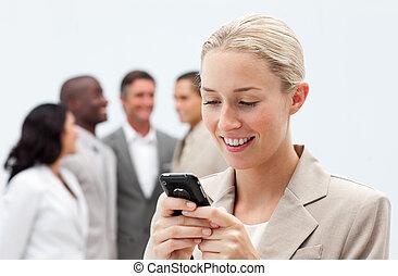 Smiling businesswoman sending a text