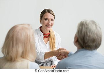 Smiling businesswoman shaking hand of senior hr at job interview