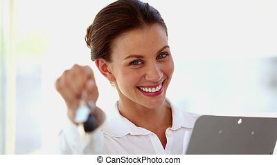 Smiling businesswoman shaking keys