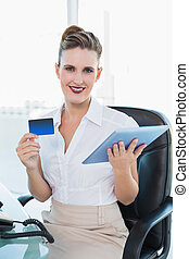 Smiling businesswoman shopping online with her tablet