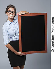 Smiling businesswoman showing the empty blackboard