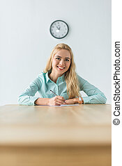 Smiling businesswoman sitting at office table