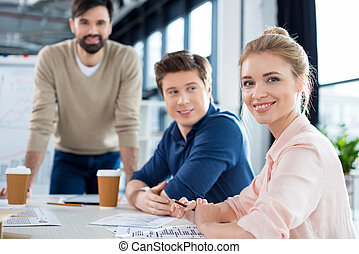 smiling businesswoman sitting at table with colleagues on business meeting