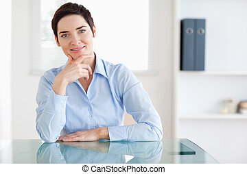 Smiling Businesswoman sitting behind a desk