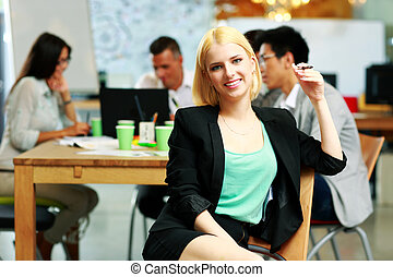 smiling businesswoman sitting in office, with her colleagues in background