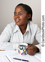 Smiling businesswoman with at her desk, holding a coffee
