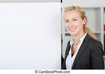 Smiling Businesswoman Standing By Flipchart In Office