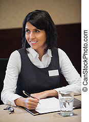 Smiling businesswoman taking notes