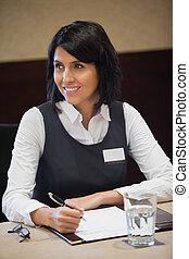 Smiling businesswoman taking notes