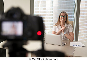 Smiling businesswoman talking on camera, lady recording business