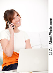 woman talking on phone and using her laptop
