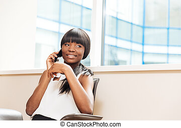 Smiling businesswoman talking on the phone in office