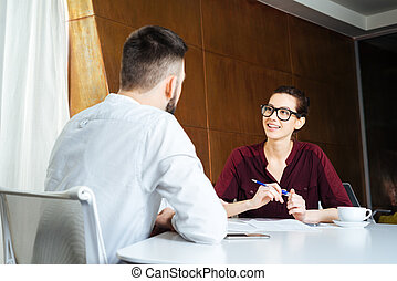 Smiling businesswoman talking to young businessman in meeting room