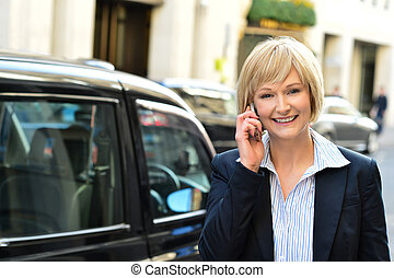 Smiling businesswoman talking via mobile
