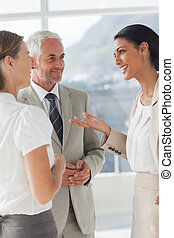 Smiling businesswoman telling something to her colleagues