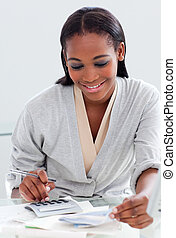 Smiling businesswoman using a calculator at her desk