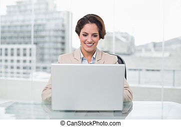 Smiling businesswoman using laptop at her desk