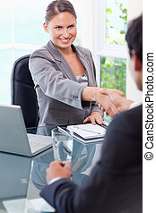 Smiling businesswoman welcomes customer in her office