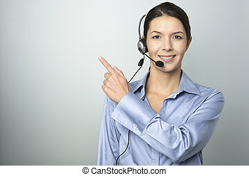 Smiling businesswoman with a headset pointing - Smiling ...
