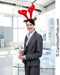Smiling businesswoman with a novelty Christmas hat drinking Champagne in the office