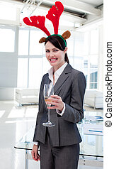 Smiling businesswoman with a novelty Christmas hat toasting with Champagne in the office