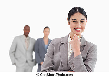 Smiling businesswoman with associates behind her